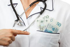 Kobiety lekarka z stetoskopu seansu połysku waluty pieniądze w fartuch kieszeni, korupci lub łapówki pojęciu, Obrazy Royalty Free