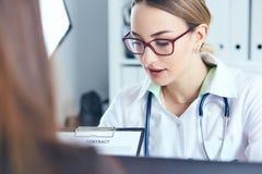 Kobiety lekarki chwyta schowka seansu dokument Fizyczny zgody formy podpis, choroby zapobieganie, odgania round zdjęcie royalty free
