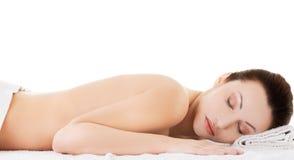 Kobiety lying on the beach na ręczniku przygotowywającym masować Fotografia Royalty Free