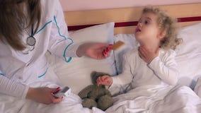 Kobiety małej dziewczynki i lekarki dziecka cierpliwy uścisk dłoni i miara temperatury zdjęcie wideo