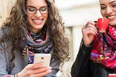 Kobiety ma kawowego i patrzeje obrazki na mądrze telefonie obrazy stock