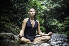 Kobiety medytuje outdoors w zieleń parku na natury tle fotografia stock