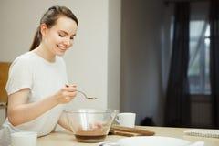 Kobiety mienia łyżka nad szklanym pucharem, przygotowanie słodki deser zdjęcia stock
