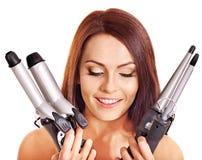 Kobiety mienia żelaza fryzowania włosy. obrazy royalty free