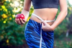Kobiety mienia czerwony jabłko z mierzyć taśmy na jej talii outdoo fotografia royalty free