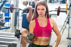 Kobiety mienia dumbbell trening przy gym Obrazy Royalty Free
