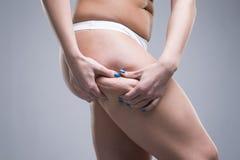 Kobiety mienia fałd skóra, celulitis na żeńskim ciele, szary tło zdjęcia stock