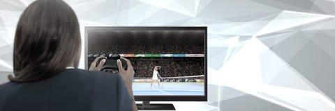 Kobiety mienia hazardu kontroler z tenisem na telewizi obraz royalty free