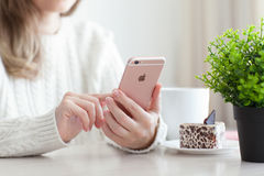 Kobiety mienia iPhone 6 S Różany złoto w kawiarni Zdjęcia Stock