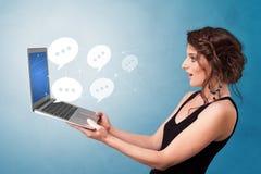 Kobiety mienia laptop z mowa bąblami zdjęcia stock