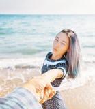 Kobiety mienia mężczyzny ręka i prowadzić on morze zdjęcia royalty free