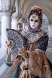 Kobiety mienia maskowy fan i być ubranym ozdobnego złoto i czarnego kostium pod łukami przy doża pałac podczas Wenecja karnawału fotografia royalty free
