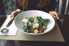 Kobiety mienia nóż dla przygotowywać jeść Caesar sałatki w restauraci i rozwidlenie obraz stock