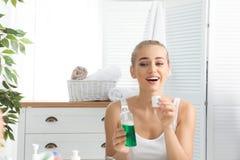 Kobiety mienia nakrętka z mouthwash w łazience i butelka obraz royalty free