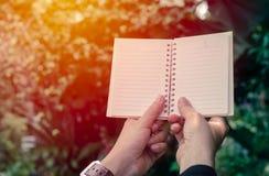 Kobiety mienia notatnik w wschodzie słońca Obrazy Stock