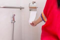 Kobiety mienia papier toaletowy i używać toaleta w ranku Zdjęcia Stock