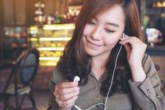 kobiety mienia piękne azjatykcie słuchawki podczas gdy słuchający muzyka zdjęcia stock