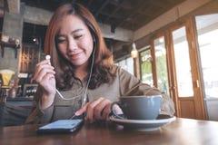 Kobiety mienia piękne azjatykcie słuchawki podczas gdy słuchający muzyka z telefonem komórkowym fotografia stock
