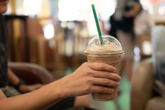 Kobiety mienia plastikowy szkło lukrowa kawa z mlekiem Zdjęcia Stock
