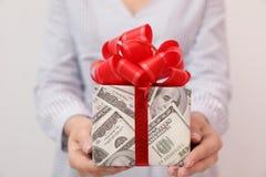 Kobiety mienia prezenta pudełko zawijający w dolarach na tle, zbliżenie obraz stock