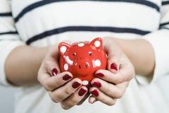 Kobiety mienia prosiątka czerwony bank fotografia royalty free