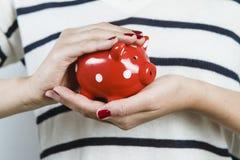 Kobiety mienia prosiątka czerwony bank obraz stock