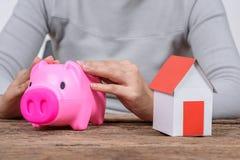 Kobiety mienia prosiątka bank i wzorcowy dom Fotografia Royalty Free