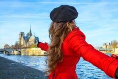 Kobiety mienia przyjaciół ręka i wskazywać przy notre dame de paris Obrazy Royalty Free