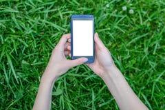 Kobiety mienia smartphone z bielu pustym ekranem sensorowym w rękach nad tłem trawa telefonu komórkowego telefonu komórkowego mob obraz royalty free