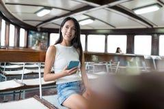 Kobiety mienia telefon komórkowy i patrzeć z okno w promu Fotografia Stock