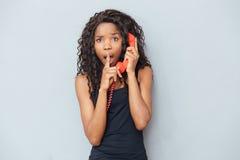 Kobiety mienia telefonu seans i tubka dotykamy nad wargami Obraz Royalty Free