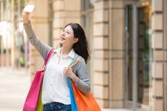 Kobiety mienia torba na zakupy podczas gdy brać autoportret fotografia stock