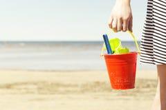 Kobiety mienia wiadro z dziecka ` s plażą bawi się - rydel i łopata na słonecznym dniu Zdjęcia Stock