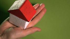 Kobiety mienia zabawki dom z czerwień dachem przeciw zielonemu tłu Agenta nieruchomości pojęcie, przestrzeń dla inskrypcj Obrazy Royalty Free