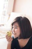 Kobiety mienia zieleni jabłko z szczęśliwy ono uśmiecha się obraz stock