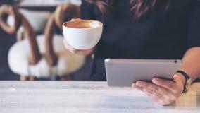 Kobiety mienie i używać pastylka komputer osobistego podczas gdy pijący kawę zdjęcia stock