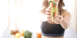 Kobiety mienie pije szklany pełnego świeża owocowa sałatka z taśmy miarą wokoło szkła Obraz Royalty Free