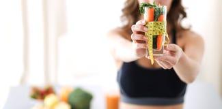 Kobiety mienie pije szklany pełnego świeża owocowa sałatka z taśmy miarą wokoło szkła Zdjęcie Royalty Free