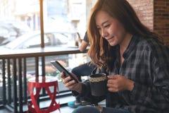 Kobiety mienie, używać mądrze telefon i patrzejący w kawiarni podczas gdy pijący kawę obrazy stock