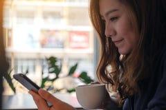 Kobiety mienie, używać mądrze telefon i patrzejący w kawiarni podczas gdy pijący kawę obraz stock