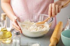 Kobiety mieszanki mąka, wypiekowy proszek, sól, olej i gorąca woda w szklanym pucharze, obraz stock