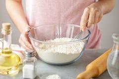 Kobiety mieszanki mąka z wypiekowym proszkiem i solą w szklanym pucharze z śmignięciem zdjęcie royalty free