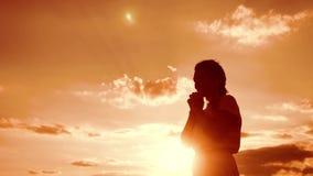 kobiety modlenie na jej kolanach Dziewczyna składał jej ręki w modlitewnej styl życia sylwetce przy zmierzchem zwolnionego tempa  zbiory