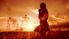 kobiety modlenie na jej kolanach dziewczyna składał jej ręki w modlitewnej sylwetce przy zmierzchem zwolnionego tempa wideo Dziew zdjęcie wideo