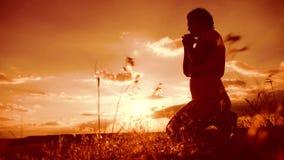 kobiety modlenie na jej kolanach dziewczyna składał jej ręki w modlitewnej sylwetce przy zmierzchem zwolnionego tempa wideo Dziew zbiory
