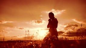 kobiety modlenie na jej kolanach dziewczyna składał jej ręki w modlitewnej sylwetce przy zmierzchem zwolnionego tempa wideo styl  zbiory wideo