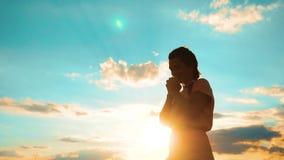 kobiety modlenie na jej kolanach dziewczyna składał jej ręki w modlitewnym sylwetka stylu życia przy zmierzchem zwolnionego tempa zbiory wideo