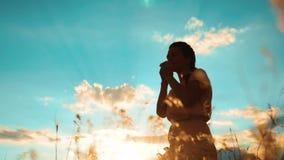 kobiety modlenie na jej stylów życia kolanach dziewczyna składał jej ręki w modlitewnej sylwetce przy zmierzchem zwolnionego temp zbiory wideo