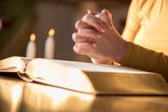 Kobiety modlenie z jej rękami nad biblią, ciężki światło fotografia royalty free