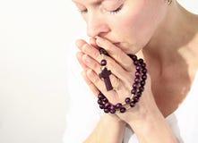 Kobiety modlenie z krzyżem w ona ręki zdjęcia stock